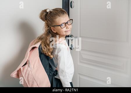 Little pretty girl 6, 7 years old with school backpack. Smiling girl standing near the front door of the house, child goes to school. - Stock Photo