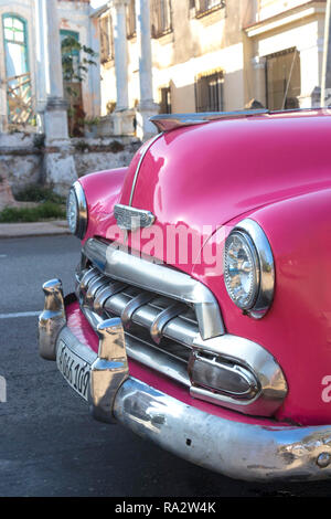 classic vintage American car parked in front of derelict houses in Havana, Cuba, Caribbean - Stock Photo