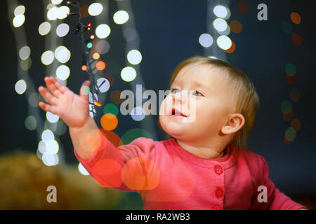 Portrait of a little girl in a pink dress in the studio. Lights Backgrounds - Stock Photo