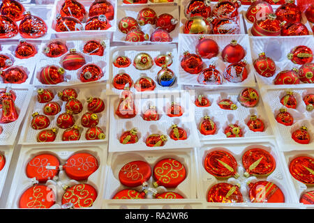 Red christmas tree balls, or bulbs, or baubles, or decorations on sale at the traditional christmas market of Strasbourg, France, Europe. - Stock Photo