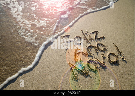 Portuguese Feliz Ano Novo (Happy New Year) message handwritten in textured lettering on smooth sand with a fresh new wave on a Brazilian beach - Stock Photo