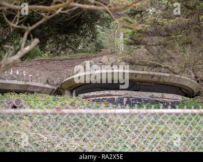 Military bunker hidden in a hill in front of steel fence - Stock Photo