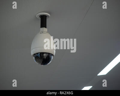 White circular surveillance camera on ceiling in a public setting attached to white ceiling - Stock Photo