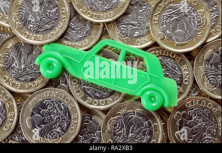 TOY CAR WITH BRITISH ONE POUND COINS RE MOTORING COSTS INSURANCE CAR BUYING SERVICING PRICES  ETC - Stock Photo