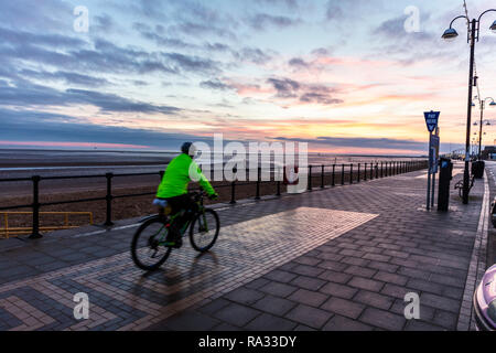Cleethorpes, Lincolnshire, UK. 31st Dec, 2018. UK Weather: Red sunrise skies in Cleethorpes, Lincolnshire, East Coast, UK. 31st Dec, 2018. Red sky making the perfect backdrop to Cleethorpes Promenade with cyclist starting his new years resolutions early, with partial cloud. Credit: Tommy (Louth)/Alamy Live News - Stock Photo