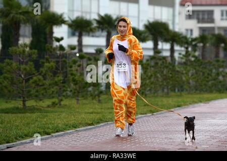 Sochi, Russia. 31st Dec, 2018. SOCHI, RUSSIA - DECEMBER 31, 2018: A woman and a dog take part in a mass run in Imeretinskaya Embankment on New Year's Eve. Artur Lebedev/TASS Credit: ITAR-TASS News Agency/Alamy Live News - Stock Photo