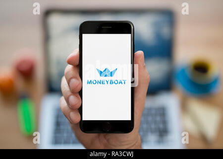 A man looks at his iPhone which displays the Moneyboat logo (Editorial use only). - Stock Photo