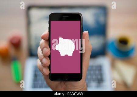 A man looks at his iPhone which displays the Piggybank logo (Editorial use only). Stock Photo