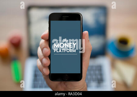 A man looks at his iPhone which displays The Money Platform logo (Editorial use only). - Stock Photo