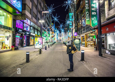 Andorra La Vieja, Andorra - Nov 5th 2017 - A young lonely woman in the street of Andorra La Vieja downtown at the night in Europe - Stock Photo
