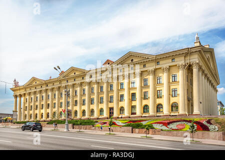 Minsk, Belarus, June 28th 2018 - A government building with flowers in front of it and a wide avenue in Minsk