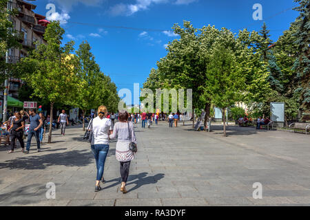 Pristina, Kosovo - May 30th 2018 - Big group of people walking in a wide pavement with big green trees and blue sky in Pristina, capital of Kosovo - Stock Photo