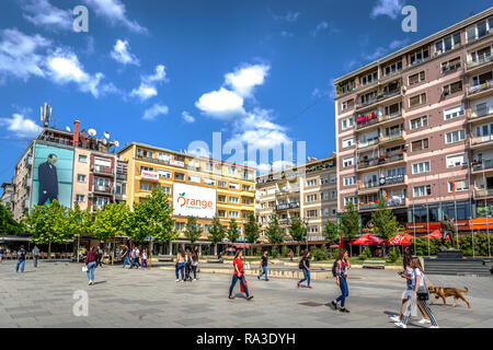 Pristina, Kosovo - May 30th 2018 - Big group of people walking in front of colorful buildings in a blue sky day in Kosovo - Stock Photo