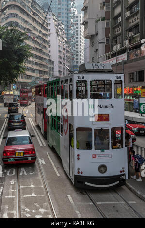 Colourful trams stop at the Fleming Road tram stop in Wan Chai with towering apartment blocks all around in this densely packed district of Hong Kong