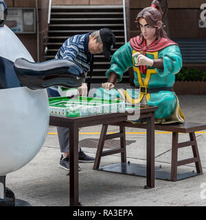 A tourist examines Liao Yuan Huo's mahjong tiles as he contests a game with On On and Guy Guy at Ani-Com Park in Hong Kong - Stock Photo