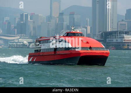 The TurboJet catamaran hydrofoil 'Penha' navigating Victoria Harbour en route to Macau with the skyscrapers of Wan Chai District in the background - Stock Photo