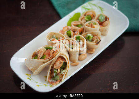 Sushi-Style Wraps with chicken pepperoni, vegetables and nuts. Healthy snacks. - Stock Photo