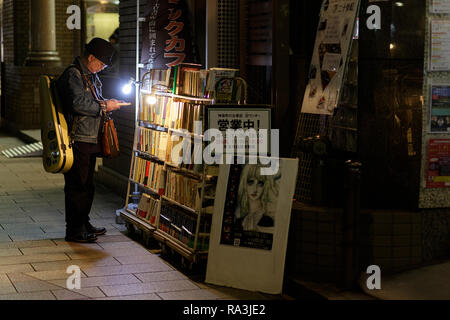 Customer reading books on the street in front of a bookstore, Jimbocho, Kanda, Chiyoda, Tokyo - Stock Photo