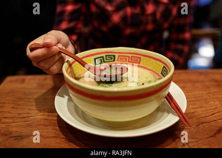 Woman holds a spoon while eating from a ramen bowl, tokyo, japan - Stock Photo