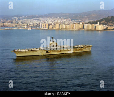 1979 - A port bow view of the aircraft carrier USS INDEPENDENCE (CV-62) anchored in the harbor. - Stock Photo
