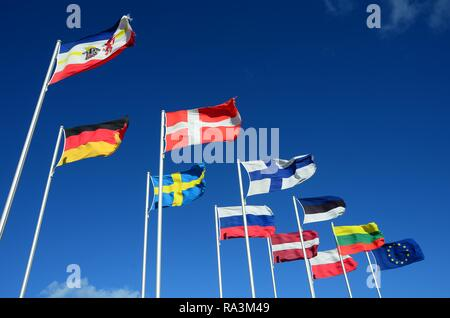 Various international flags against a blue sky, Mecklenburg-Western Pomerania, Germany - Stock Photo