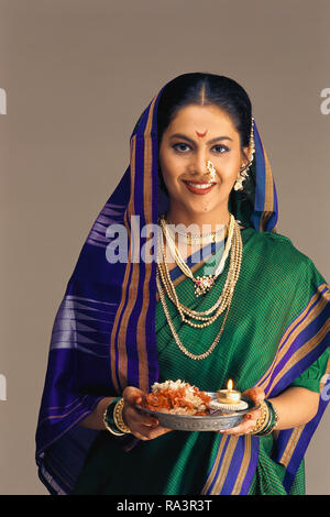 A PORTRAIT OF A MARATHI/MAHARASHTRIAN Bride dressed in traditional SAREE, HOLDING A PUJA THALI/ CEREMONIAL VESSEL WITH A LIT LAMP. - Stock Photo