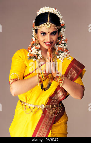 A PORTRAIT OF A South Indian Bride dressed in traditional costume, GREETING WITH HANDS FOLDED (NAMASTE) - Stock Photo