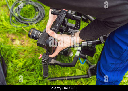 Cameraman setting up heavy duty professional 3-axis gimbal stabilizer for cinema camera - Stock Photo