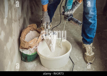 Young male painter kneads putty with water in a bucket using a hand-held mixer for building mixes - Stock Photo