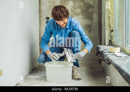 master is applying white putty on a wall and smearing by putty knife in a room of renovating house in daytime - Stock Photo