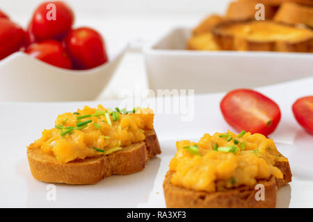 White plate with toasts and scrambled eggs, chive herbs and cherry tomatoes on white table background. Grilled bread with scrambled eggs and vegitable - Stock Photo
