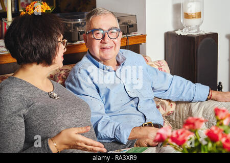 happy seniors couple sitting on the couch in a floral pattern at home - Stock Photo