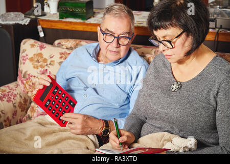 Couple of seniors doing household accounting with calculator and planning at home. - Stock Photo