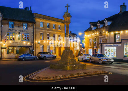 The floodlit market square and stone cross at nighttime  in the Cotswold town of Stow on the Wold Gloucestershire England UK - Stock Photo