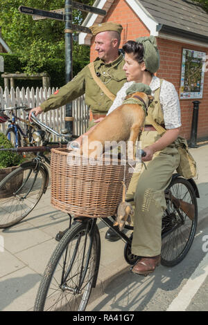 Summer, Woodhall Spa 1940s Festival. Man, woman and dog dressed up in authentic 1940's dress, celebrating life on the home front during the war years. - Stock Photo