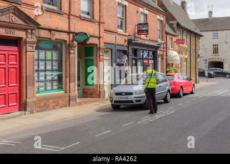 Civil Enforcement Officer checking possible illegal parking, in designated disabled parking spaces. Rutland, England, UK - Stock Photo