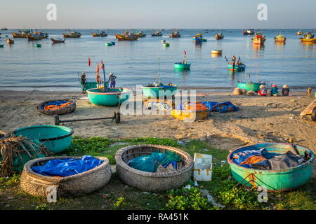 fishermen village in Phan Thiet Vietnam. Traditional Vietnamese boats in fishing port and fishermen trading fish products in the fishing village - Stock Photo