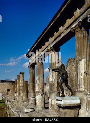 Italy. Pompeii. Temple of Apollo. Architectural detail of the colonnade and bronze statue of Apollo (copy of Apollo Saettante). Cult is attested in since 6th century BC. The sanctuary presents the appearance that it had after being rebuilt in 2nd century BC. Another reconstruction was necessary to repair the damages because of the earthquake in 62. Campania. - Stock Photo