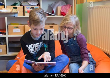 Two students in elementary school reading a book, sitting on beanbag, Lower Saxony, Germany - Stock Photo
