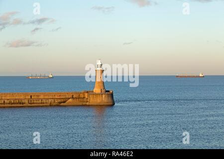 Lighthouse, cargo ships at sea, Tynemouth, Northumberland, Great Britain - Stock Photo