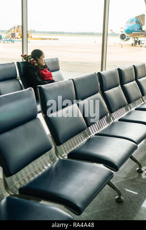 Young Asian woman sit on bench in airport terminal - Stock Photo