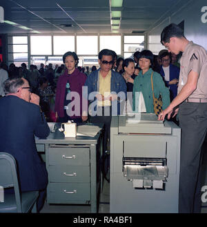 1975 - Vietnamese refugees evacuated from Saigon are processed at the air station passenger terminal before departing for Marine Corps Base, Camp Pendleton. - Stock Photo