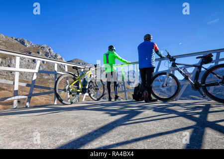 Two cyclists with their mountain bikes looking at the landscape from a viewpoint they found on their way. - Stock Photo