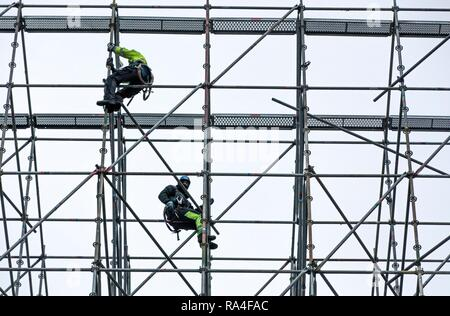 Scaffolders at work, building a large scaffolding, work at high altitude, Germany - Stock Photo