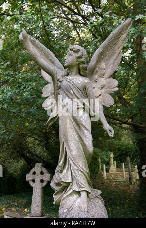 Statue angel in graveyard East Highgate cemetery London England - Stock Photo