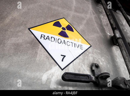 Radiation warning sign on the Hazardous materials transport label Class 7 at the aluminum container of transport truck - Stock Photo