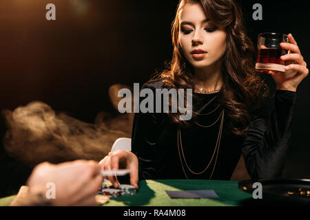 attractive girl holding glass of whiskey at poker table in casino - Stock Photo