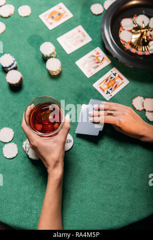 cropped image of girl playing poker and holding glass of whiskey at table in casino - Stock Photo