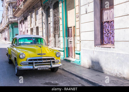 classic yellow vintage American car parked on road in Havana, Cuba, Caribbean - Stock Photo