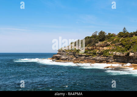 Cliffs at the coastal walk from Bondi beach to Coogee beach in Sydney on a perfect blue day in summer (Sydney, New South Wales, Australia) - Stock Photo